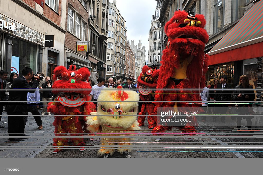 Chinese lions open the way on July 6, 2012 in Brussels to Belgian and Chinese personalities, heading to attend a ceremony at the nearby famous Manneken-Pis fountain. The bronze boy that pees into a fountain was dressed for the first time on July 6 in a traditional Hong Kong costume, including a Zhongshan suit and a clipboard under his arm.