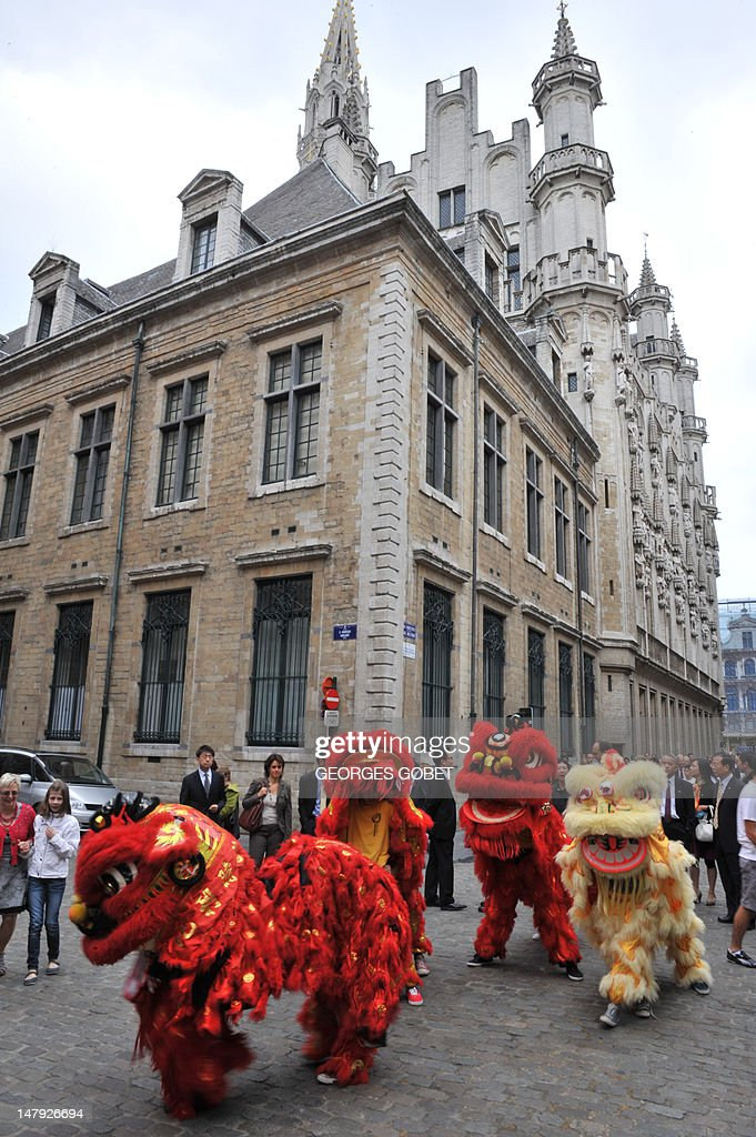 Chinese lions open the way on July 6, 2012 on the Grand Place in Brussels to Belgian and Chinese personalities, heading to attend a ceremony at the nearby famous Manneken-Pis fountain. The bronze boy that pees into a fountain was dressed for the first time on July 6 in a traditional Hong Kong costume, including a Zhongshan suit and a clipboard under his arm. AFP PHOTO / GEORGES GOBET