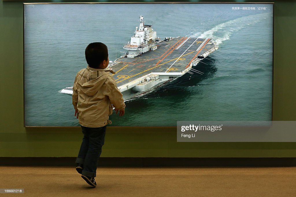 A Chinese little boy passes the photo of China's first aircraft carrier as visiting an exhibition entitled 'Scientific Development and Splendid Achievements' before the18th National Congress of the Communist Party of China (CPC) on October 30, 2012 in Beijing, China. The exhibition showcases China's progress in political, economic, cultural and ecological spheres over the past decade. The18th National Congress of the Communist Party of China (CPC) is proposed to convene on November 8 in Beijing.