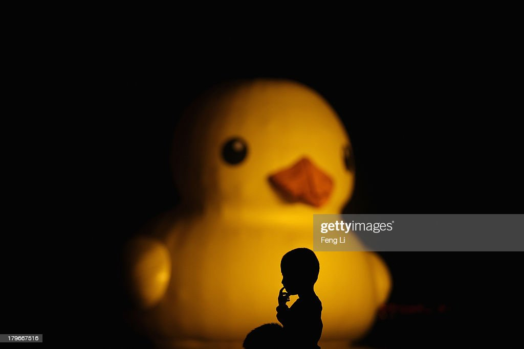 A Chinese little boy sits on his father's shoulder to see a 18 meters high rubber duck at Beijing Garden Expo Park on September 6, 2013 in Beijing, China. After touring 13 cities in 10 countries, a gaint rubber duck designed by Dutch artist Florentijn Hofman will float first at Beijing Garden Expo Park and then at the Summer Palace from September to October in Beijing.