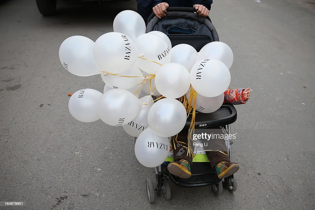 A Chinese little girl takes the balloons on the third day of Mercedes-Benz China Fashion Week Autumn/Winter 2013/2014 at 751 D.PARK Workshop on March 26, 2013 in Beijing, China.