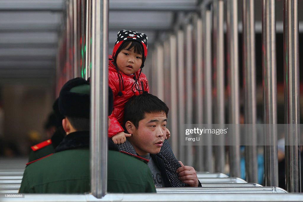 A Chinese man and his daughter pass the check-in kiosks for real-name tickets as Chinese paramilitary policemen guarding at Beijing West Railway Station on January 8, 2012 in Beijing, China. China's annual Spring Festival travel rush begins on Sunday, and authorities estimate 3.158 billion passenger journeys will be made for the Chinese lunar new year during the 40-day travel period.