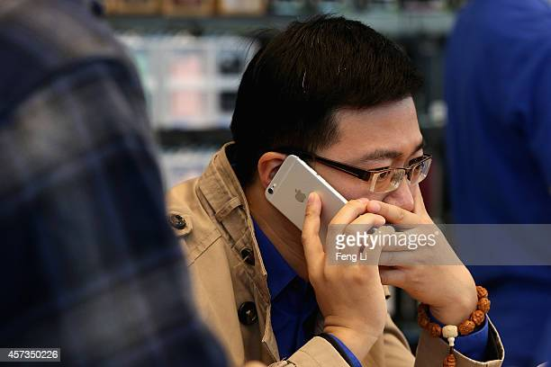Chinese man answers the phone with his new iPhone 6 Plus inside an Apple store on October 17 2014 in Beijing China Apple Inc began delivering its...