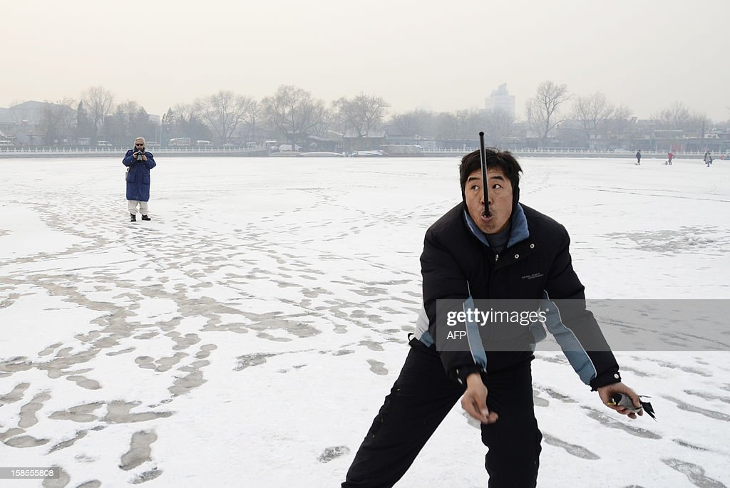 A chinese man bites a blowgun as he prepares to toss his pet bird into the air as part of a game on a frozen lake in Beijing on December 19, 2012. China will allow transit passengers from 45 countries including the US, Canada and all members of the EU to spend up to 72 hours in Beijing without a visa from January 2013, city authorities said. AFP PHOTO / WANG ZHAO