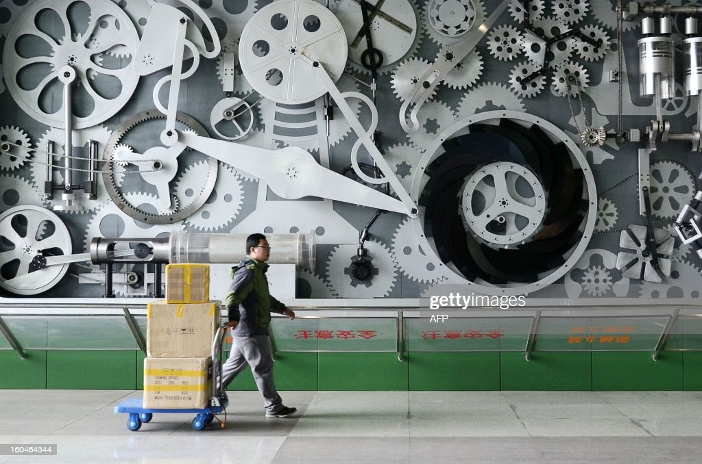 A Chinese man carries goods on a trolley as he walks past mechanic installation at a museum in Beijing on February 1 , 2013. Manufacturing activity in China expanded in January, two separate surveys showed on February 1, but they differed on whether the recovery was slowing or accelerating.
