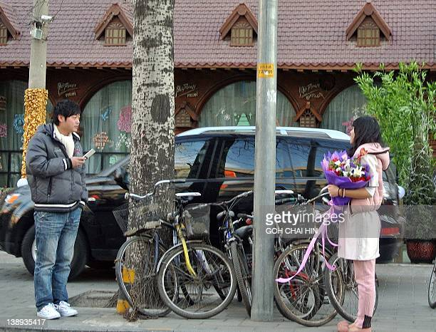 A Chinese man chats with woman after giving her a bouquet of flowers on Valentine's Day along a street in Beijing on February 14 2012 Young Chinese...