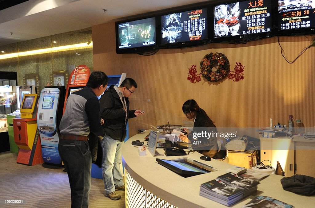 A Chinese man (2nd L) checks a movie ticket in front of the ticket office at a cinema in Beijing on January 10, 2013. Moviegoers in China spent 17 billion yuan (2.7 billion USD) on tickets last year, turning the country into the second-largest film market in the world, the state news agency Xinhua said on January 9.