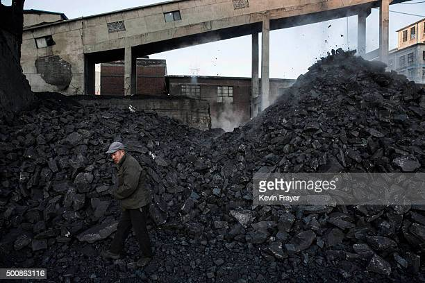 SHANXI CHINA NOVEMBER 25 A Chinese man collects coal in a sorting area at a coal mine on November 25 2015 in Shanxi China A history of heavy...