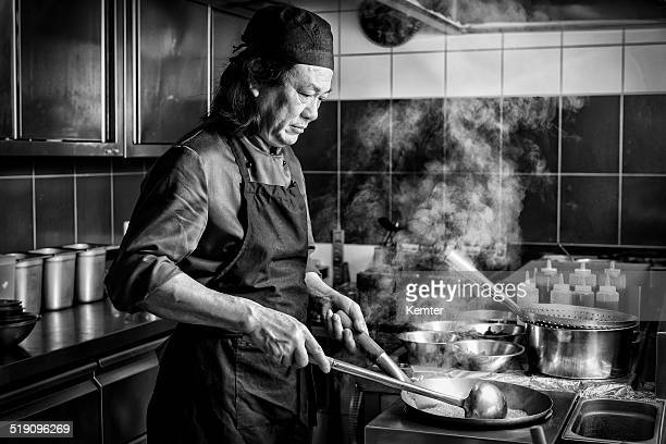 chinese man cooking in asian restaurant