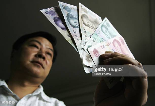 A Chinese man displays new issued yuan notes at a bank on August 31 2005 in Shanghai China Authorities issued new yuan notes today that largely...
