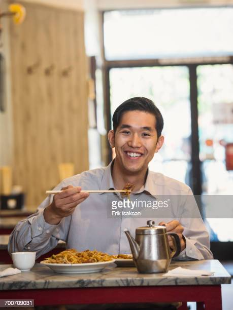Chinese man eating with chopsticks in restaurant