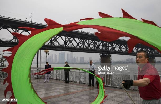 Chinese man exercises with a dragon as men watch along the Great Bridge on the Yangtze River or Chang Jiang on May 16 2017 in Wuhan Hubei province...