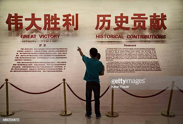 Chinese man gestures to his child at a display saying 'Great Victory' during a visit to the Museum of the War of Chinese People's Resistance Against...