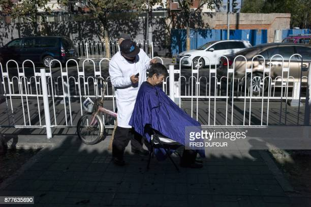 Chinese man has his hair cut by a barber in a street in Beijing on November 23 2017 / AFP PHOTO / FRED DUFOUR