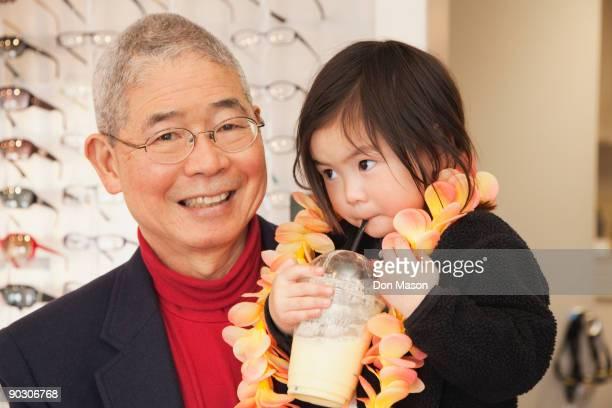 Chinese man holding granddaughter