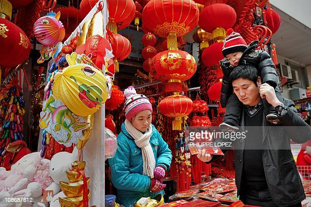 A Chinese man holding his son on his shoulders buys Lunar New Year decorations in Shanghai on February 1 2011 China's 13 billion inhabitants will...