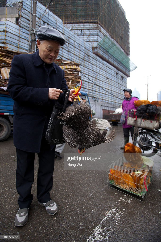 A Chinese man holds a bought cock at an outdoor market on February 5, 2013 in Shanghai, China. Chinese citizens are stocking up on food ahead of the upcoming Chinese Lunar New Year, also known as Spring Festival, is one of the most important festivals in China and falls this year on February 10, 2013.