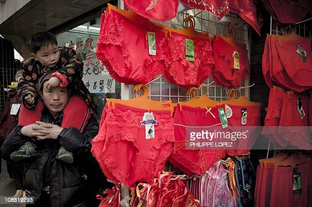 A Chinese man holds a boy on his shoulders next to red underwear displayed in a shop on the first day of the Chinese Lunar New Year in Shanghai on...