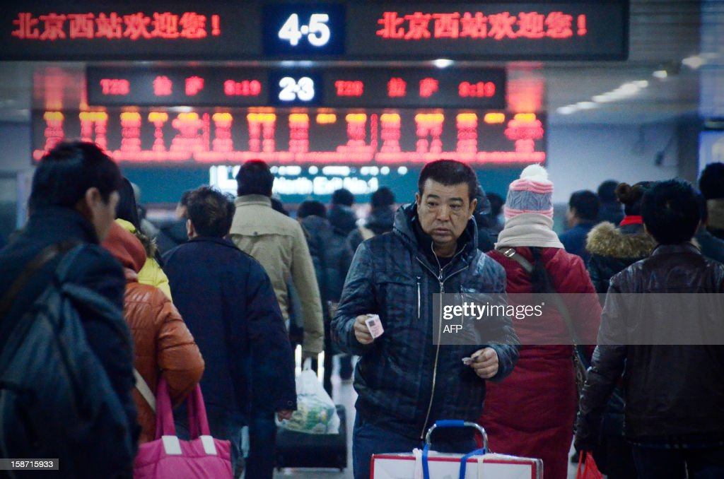 A Chinese man holds a ticket to be checked at an exit of the Beijing west railway station in Beijing on December 26, 2012. China on December 26 started service on the world's longest high-speed rail route, the latest milestone in the country's rapid and sometimes troubled super fast rail network.