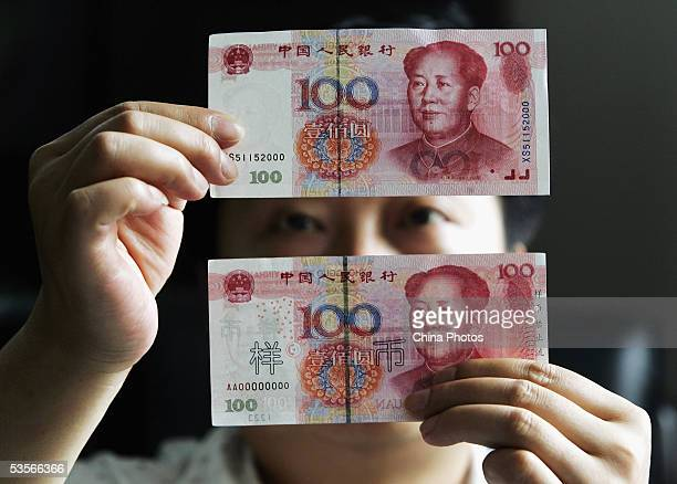A Chinese man identifies a new issued 100 yuan note with an old one issued in 1999 at a bank on August 31 2005 in Shanghai China Authorities issued...