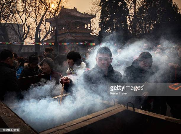 A Chinese man is shrouded in smoke from incense as he lights a stick while praying with others at the Yonghegong Lama Temple during celebrations for...