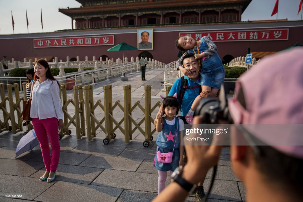 A Chinese man jokes as he has his picture taken with kids outside the Forbidden City at Tiananmen Square on June 2, 2014 in Beijing, China. Twenty-five years ago on June 4, 1989, Chinese troops cracked-down on pro-democracy protesters leaving scores dead and injured.