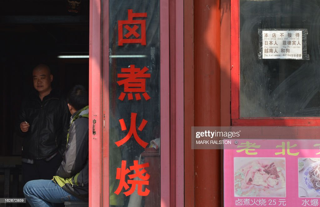 A Chinese man looks out from a restaurant that displays a sign saying (R) 'This shop does not receive the Japanese, The Philippines, The Vietnamese and Dog' at the historic tourist district of Houhai in Beijing on February 26, 2013. China is currently in border disputes with Japan, Vietnam and the Philippines and has grown increasingly assertive in recent years in claiming islands and waters even without effective control of them -- in some cases hundreds of kilometres from the Chinese mainland and close to rival claimants' coasts. AFP PHOTO/Mark RALSTON