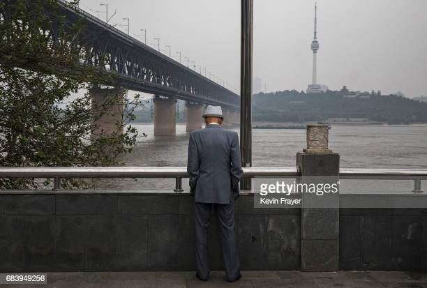 Chinese man looks out towards the Great Bridge over the Yangtze River or Chang Jiang on May 16 2017 in Wuhan Hubei province China