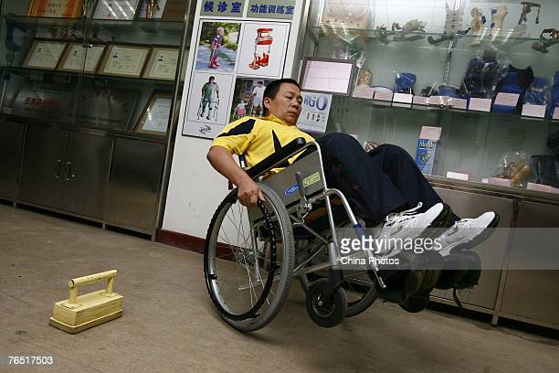 Chinese man Peng Shuilin whose body was severed in half in a traffic accident controls his wheelchair to round a barrier before he leaves the China...