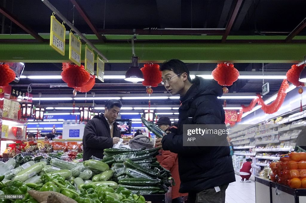 A Chinese man picks up vegetables at a market in Beijing on January 11,2013 . China's inflation rate slowed to 2.6 percent in 2012, the National Bureau of Statistics said on January 11, down sharply from 5.4 percent the year before.