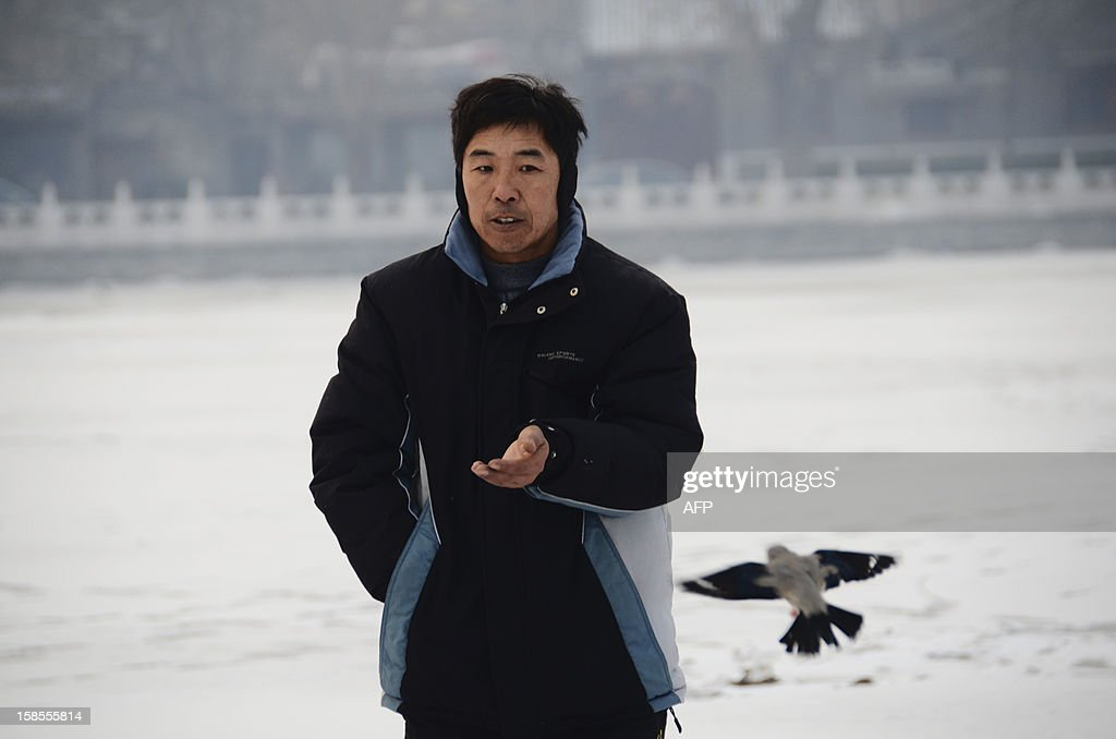 A Chinese man prepares to feed his pet bird on a frozen lake in Beijing on December 19, 2012. China will allow transit passengers from 45 countries including the US, Canada and all members of the EU to spend up to 72 hours in Beijing without a visa from January 2013, city authorities said. AFP PHOTO / WANG ZHAO