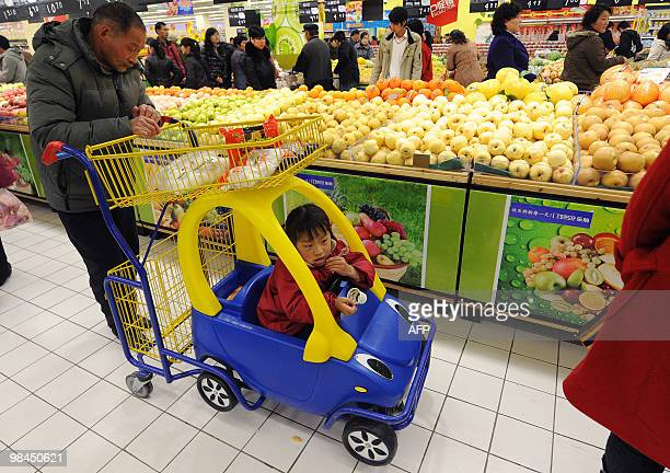 A Chinese man pushes a child in a cart while shopping at a supermarket in Hefei central China's Anhui province on April 13 2010 The Asian Development...