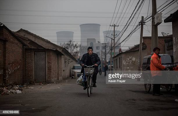 Chinese man rides a bicylce as a coal fired power plant is seen in the background on November 19 2014 in Beijing China United States President Barack...