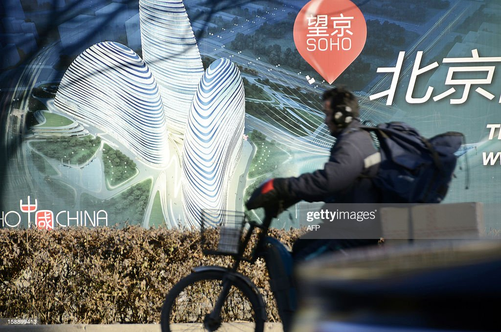 A Chinese man rides a tricycle past a billboard for the under-construction Wang Jing SOHO complex by renowned architect Zaha Hadid in Beijing on January 3, 2013. Already famed for fake designer bags and pirated DVDs, imitation in China may have reached new heights with a set of towers that strongly resemble ones designed by renowned architect Zaha Hadid. It could rank among the more flagrant ripoffs in a country already notorious for imitating foreign products without permission -- but the developer of the Chongqing project, Meiquan 22nd Century, has denied any copying.