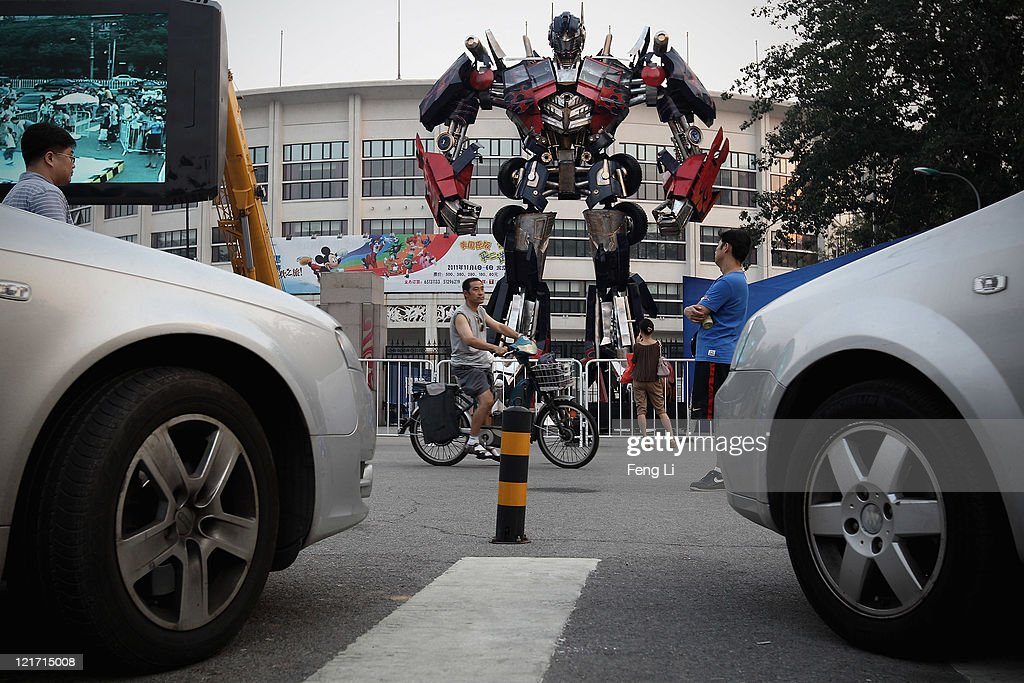 Chinese man rides bicycle passing by the transformer model Optimus Prime displayed for a promotion outside Beijing Workers' Gymnasium on August 22...