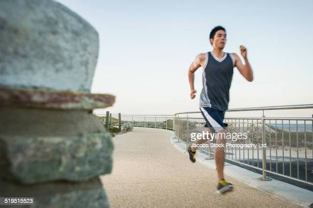 Chinese man running on waterfront path