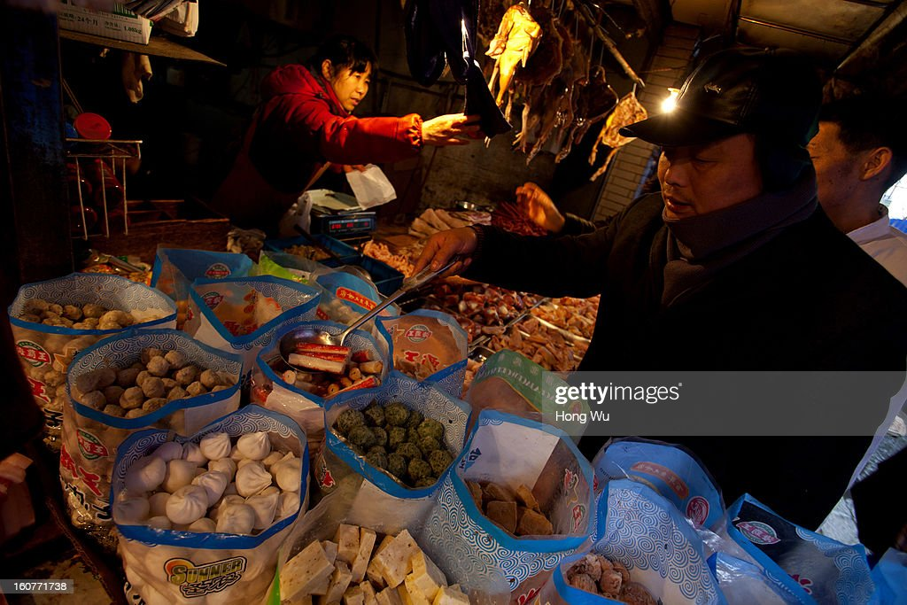 A Chinese man selects produce stall at an outdoor market on February 5, 2013 in Shanghai, China. Chinese citizens are stocking up on food ahead of the upcoming Chinese Lunar New Year, also known as Spring Festival, is one of the most important festivals in China and falls this year on February 10, 2013.
