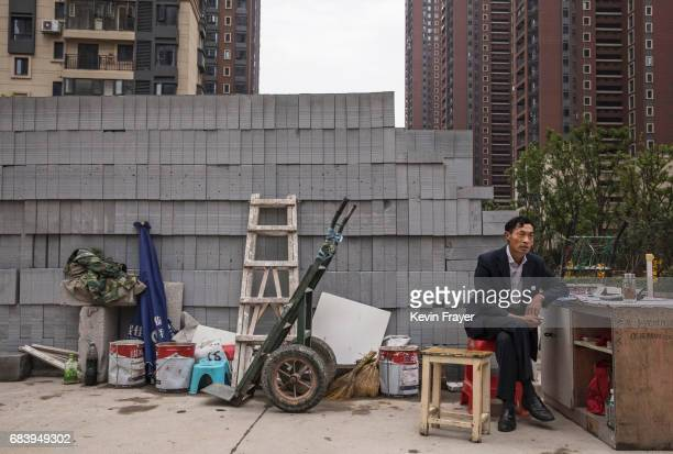 Chinese man sits at a desk selling bricks at a construction site for a new development on May 15 2017 in Wuhan Hubei province China