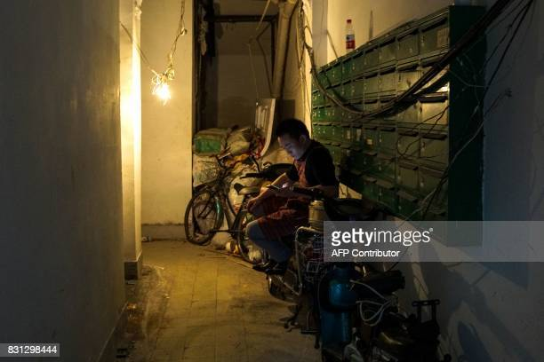 A Chinese man sits on a scooter inside a garage in Shanghai on August 14 2017 / AFP PHOTO / CHANDAN KHANNA