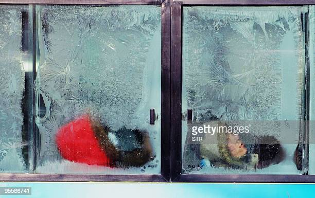 A Chinese man sleeps against an icefrosted window as he rides a bus after a heavy snowfall in Beijing on January 4 2010 Heavy snow has brought more...