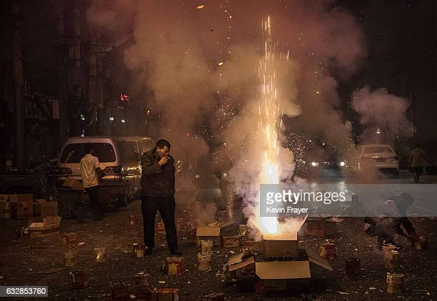 Chinese man smokes a cigarette as he and others set off firecrackers a traditional way of warding off evil spirits in celebration of the Chinese...