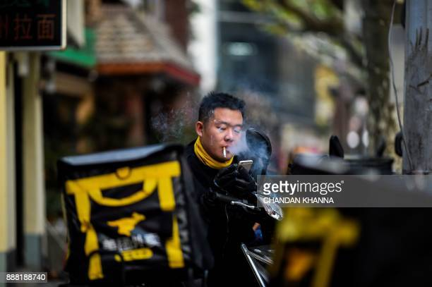 A Chinese man smokes a cigarette as he uses his mobile phone in Shanghai on December 8 2017 / AFP PHOTO / CHANDAN KHANNA