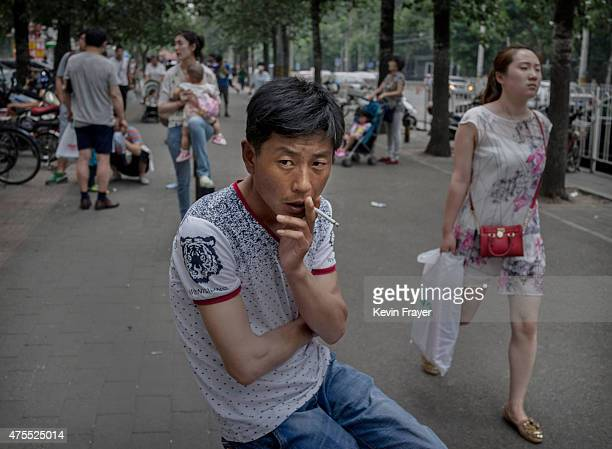 Chinese man smokes a cigarette in a prohibited area outside a children's hospital on June 1 2015 in Beijing China Beijing introduced strong new...