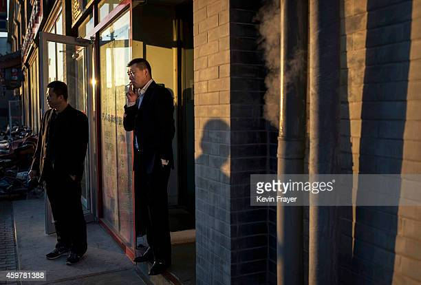 Chinese man smokes a cigarette outside an office on December 1 2014 in Beijing China There are more than 300 million smokers in the world's most...