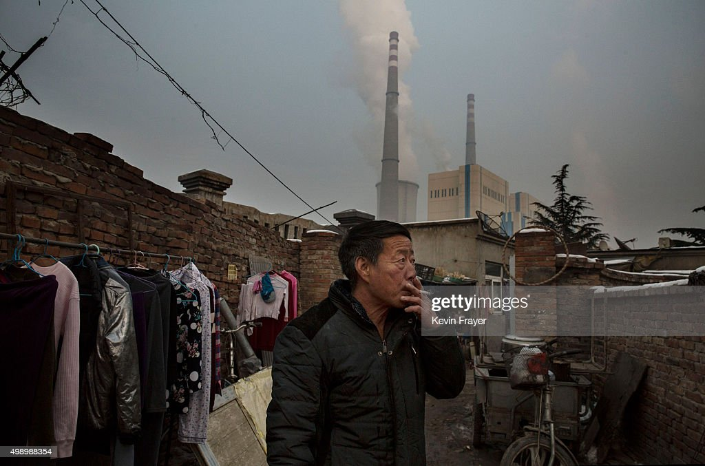 Chinese man smokes in front of his house next to a coal fired power plant on November 27 2015 on the outskirts of Beijing China China's government...