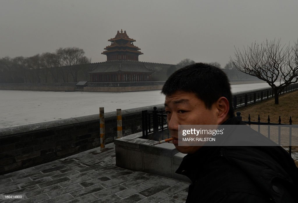 A Chinese man smokes in front of the Forbidden City as smog continues to shroud Beijing on January 31, 2013. Doctors in Beijing said on January 31 that hospital admissions for respiratory complaints rose in recent days during the latest bout of air pollution to cover northern China. AFP PHOTO/Mark RALSTON