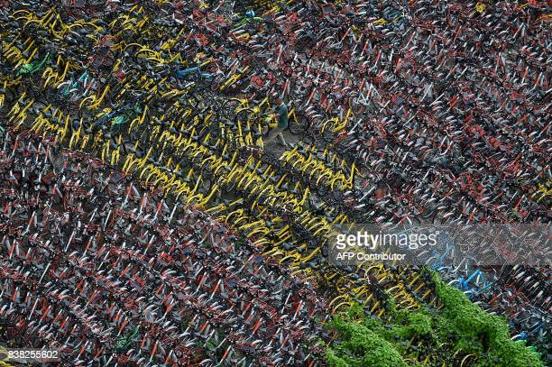 A Chinese man sorts abandoned share bicycles stored at a temporary parking lot in Shanghai on August 24 2017 The bikesharing industry has proven...