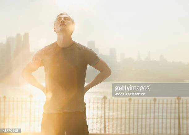 Chinese man standing by urban river