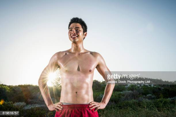 Chinese man standing with hands on hips near sunny hill