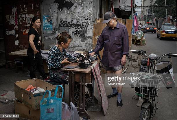 Chinese man stands in his boxer shorts as she has his pants repaired at a street tailor in a residential neighborhood on May 28 2015 in Beijing China